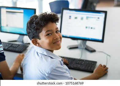 Young happy schoolboy using computer. Arab child learning to use computer at elementary school. Portrait of smiling middle eastern kid looking at camera while surfing the net in school library.