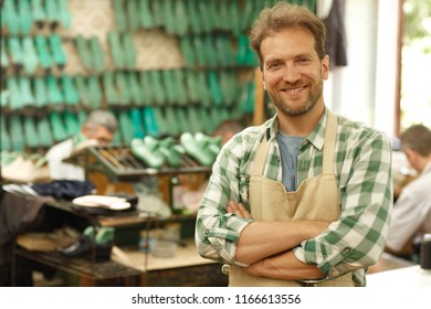 Young happy sewing master standing with crossed arms on chest at sewing factory. Bearded man smiling and looking at camera with shelves green plastic pads using for making shoes on blur background.
