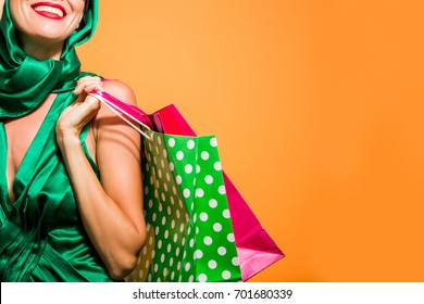 Young happy shopping woman with shopping bags isolated over bright background, copy space