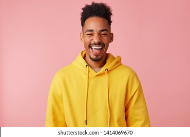 Young happy smiling african american guy in yellow hoodie, heard a very funny joke and laughed, standing on a pink background with eyes closed.