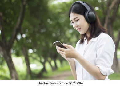 Young happy smiling Asian woman listening music with headphones in the natural