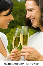 Young happy smiling attractive amorous couple celebrating with champagne together, outdoors. Love, flirt, romantic, relations theme concept.