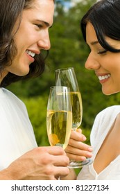 Young happy smiling attractive amorous couple celebrating with champagne together, outdoors