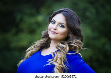 Young happy smiling beautiful plus size model in blue dress outdoors, xxl woman on nature, professional makeup and hairstyle, close-up portrait