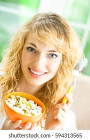 Young happy smiling beautiful woman eating muesli at home