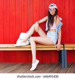 Young happy smiling brunette tan woman posing outdoor in summer time wearing vintage pink top, jeans shorts and American flag sunglasses sitting on wooden bench at red background. USA. Outdoor.