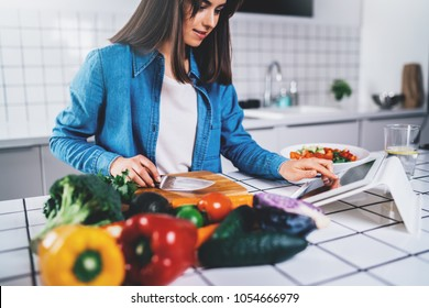 Young happy smiling brunette woman using digital tablet while cooking vegan food in the modern kitchen, smiling hipster girl preparing healthy vitamin salad with vegetables, eating healthy lifestyle
