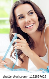 Young happy smiling brunette woman with measure tape, indoors. Healthy eating, beauty and dieting concept.