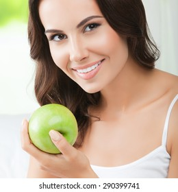 Young happy smiling brunette woman with green apple, indoors. Healthy eating, beauty and dieting concept.