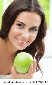 Young happy smiling brunette woman with green apples, indoors. Healthy eating, beauty and dieting concept.