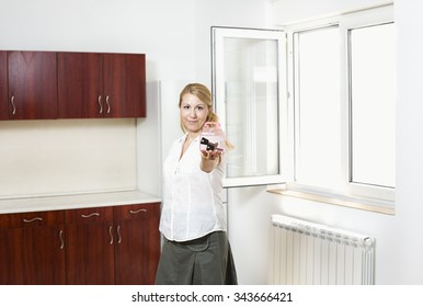 Young happy smiling business woman or real estate agent showing keys from new house