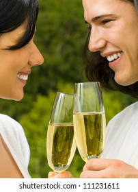 Young happy smiling cheerful attractive couple celebrating with glasses of champagne, outdoor
