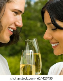 Young happy smiling cheerful attractive couple celebrating with glasses of champagne, outdoor. Love, romantic and relations concept.