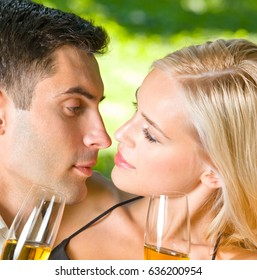 Young happy smiling cheerful attractive couple celebrating with glasses of champagne, outdoor. Love and relationships concept.