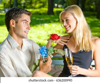 Young happy smiling cheerful attractive couple celebrating with glasses of champagne and rose, outdoors. Love and relationships concept.