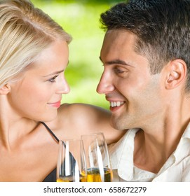 Young happy smiling cheerful attractive couple celebrating with glasses of champagne, outdoor. Love, relationships and dating concept.