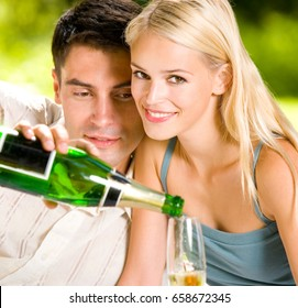 Young happy smiling cheerful attractive couple celebrating with champagne, outdoor. Love, relationships and dating concept.