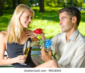 Young happy smiling cheerful attractive couple celebrating with glasses of champagne and rose, outdoors