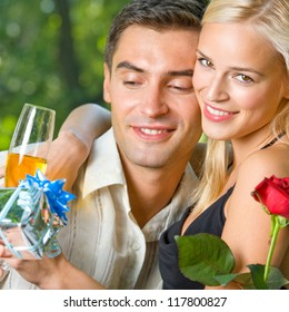 Young happy smiling cheerful couple with gifts, rosa and champagne, outdoor