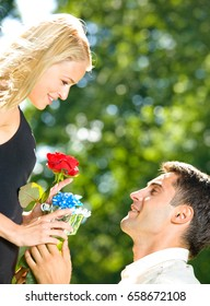 Young happy smiling cheerful couple with gifts, rosa and champagne, outdoor. Love, relationships and dating concept.