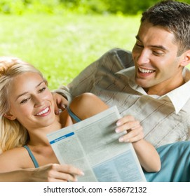 Young happy smiling cheerful couple reading together newspaper, outdoor. Love, relationships and dating concept.