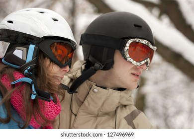 Young happy smiling couple in helmets and gogles