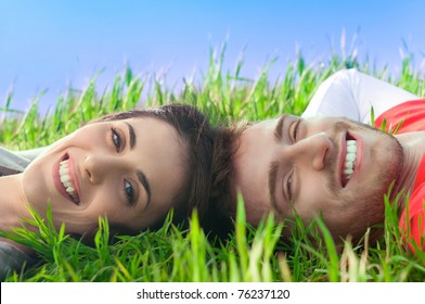 Young happy smiling couple looking at camera lying in the grass outdoor