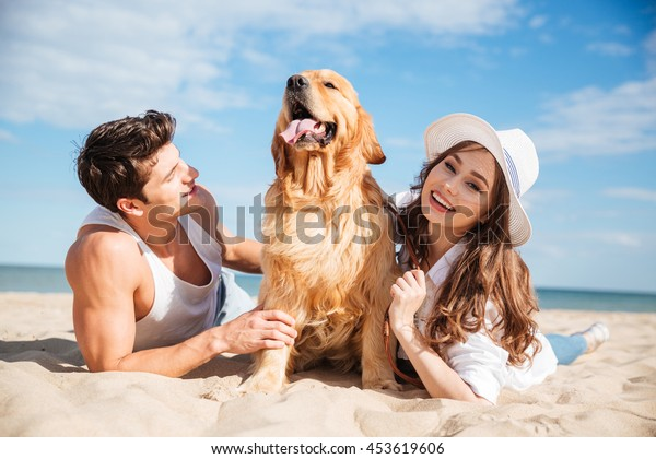 Young happy smiling couple in love lying on the beach with dog