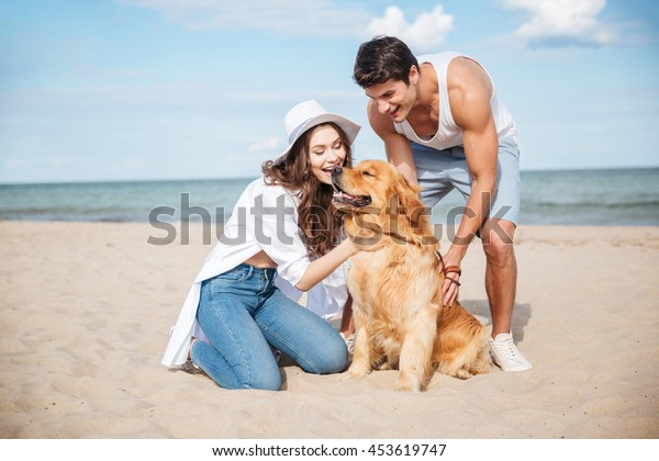 Young happy smiling couple in love sitting on the beach with dog