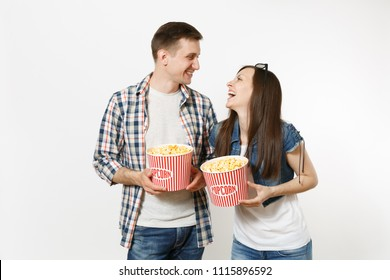 Young happy smiling couple, woman and man in 3d glasses and casual clothes watching movie film on date, holding buckets of popcorn, laughing isolated on white background. Emotions in cinema concept