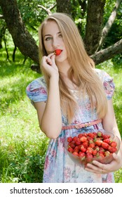 Young happy smiling & looking at camera teen girl eating strawberry from huge bowl on summer day outdoors
