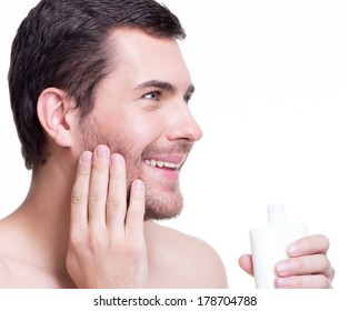 Young happy smiling man applying cream lotion on face - isolated on white.