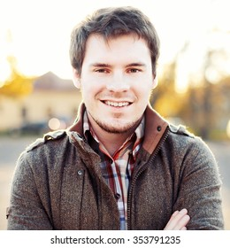 Young happy smiling man outdoor closeup hipster portrait
