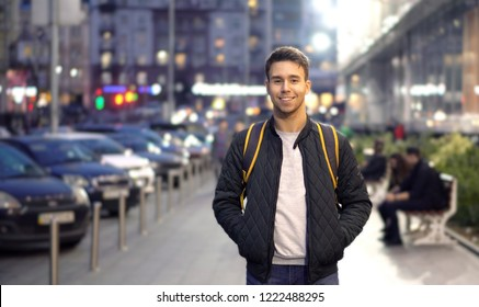 Young happy smiling man standing in the evening street