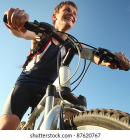 Young happy and smiling man standing with bicycle and looking to somewhere