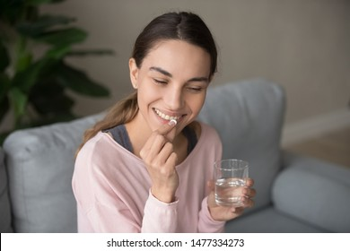 Young happy smiling mixed race woman sitting on a sofa at living room, holding glass of pure water, taking daily vitamin d, c complex, supplements for hair, skin and nail strengthen, healthcare