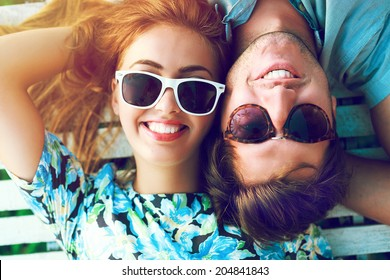 Young happy smiling pretty couple posing in hot summer day, wearing retro sunglasses, blonde beautiful girl and her handsome boyfriend.