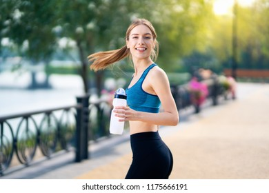Young happy smiling woman with bottle of water, during morning jogging outdoors on sunrise light. Fitness, sport, exercising and workout in city concept. Copy space empty area for some text or slogan.