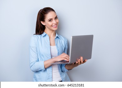 Young happy smiling woman in casual clothes holding laptop and sending email to her best friend