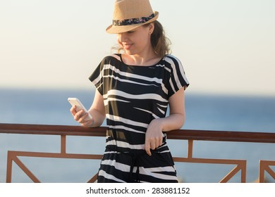 Young happy smiling woman in cute straw hat and casual summer dress leaning on railing on sunny street of sea town, holding cellphone, looking at screen, using app, messaging