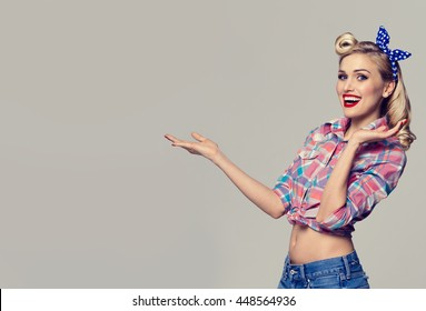 Young happy smiling woman, dressed in pin-up style, showing something or copyspace area for text or slogan. Caucasian blond model posing in retro fashion and vintage concept studio shoot.