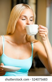 Young happy smiling woman drinking coffee, at home. Caucasian blond model in home leisure and happiness concept.