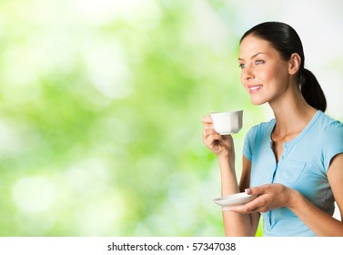 Young happy smiling woman drinking coffee, outdoors. You can use left part for slogan, big text or banner.