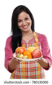 Young happy smiling woman holding basket of fruits