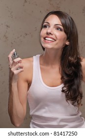 Young happy smiling woman holding perfume bottle and looking away