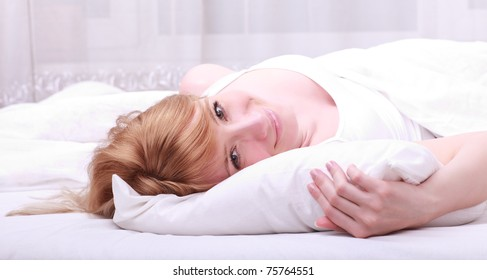 Young happy smiling woman on bed at morning