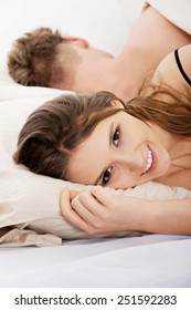 Young happy smiling woman and sleeping man in bed.