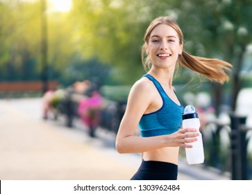 Young happy smiling woman in sportswear, with bottle of water, during morning jogging, outdoors. Fitness, sport, exercising and workout in city concept. Copy space for some text or slogan.