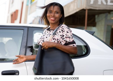 Young happy smiling woman standing in front of a new luxury car and presenting the car by the right hand outside.