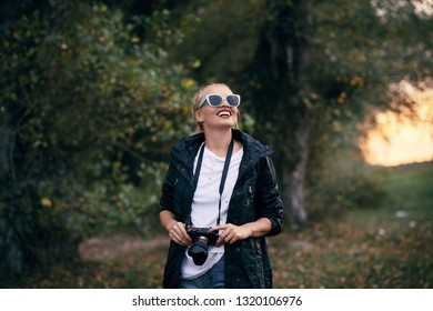 A young and happy smiling woman takes pictures of nature in the forest.
